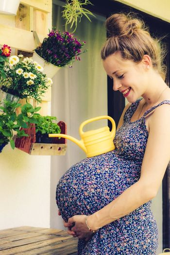 pregnant woman with huge belly and watering can Young Woman Funny Fooling Around Pregnant Belly  Pregnant Watering Can Florist Watering Balcony Potted Plants Beautiful Woman Home Women One Person Plant Lifestyles Real People Young Adult Smiling Happiness Adult Leisure Activity Casual Clothing Beauty Beautiful Woman
