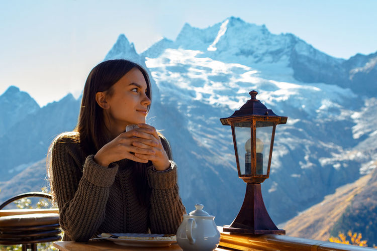 Young woman drinking coffee on street against mountains during winter
