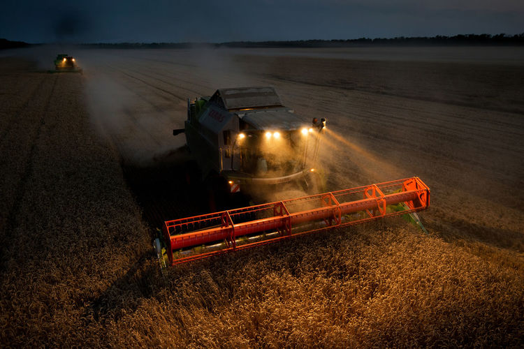 High Angle View Of Illuminated Combine Harvester On Farm