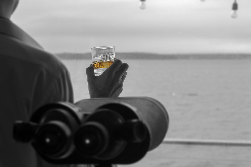 Man searching the sea while holding a alcoholic cocktail with ice Adult Alcohol Beach House Beverage Businessman Close-up Day Drink Holding Ice Lifestyles Masculine Mobile Phone One Person Outdoors Professional Real People Water Whiskey