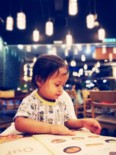 Cute baby girl looking at menu while sitting in illuminated restaurant
