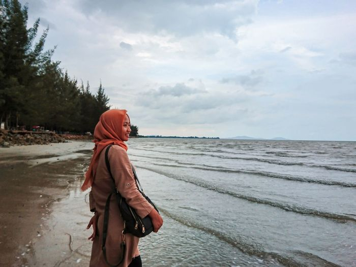Side view of woman looking away while standing on beach against sky