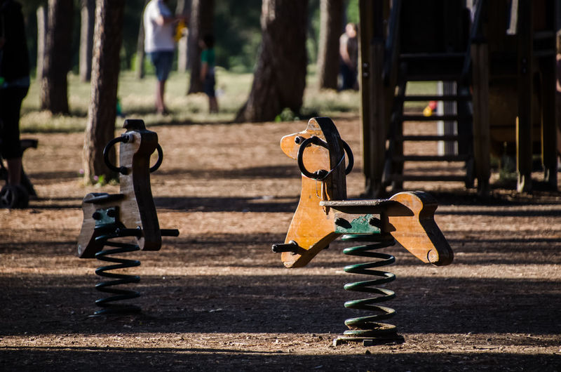 Close-up of rocking horses in park during sunny day