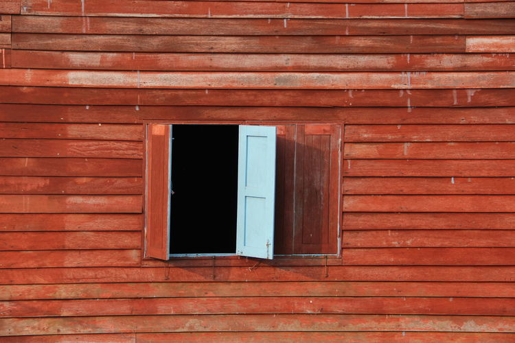 Low angle view of window on wooden wall of building