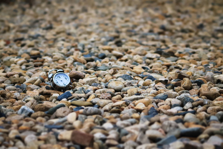 Alarm clock on pebbles at beach