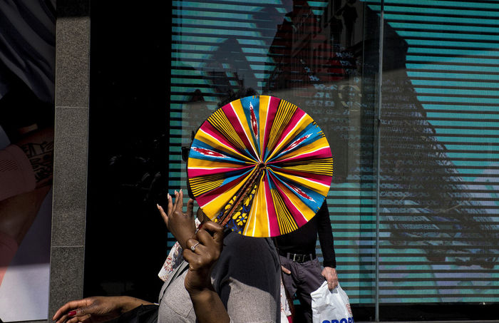 A woman walking in London with a colourful folding fan decorated with African patterns in Oxford Circus on 21th April 2018 in London, United Kingdom. Oxford Circus and Regent Street are highly popular for its shopping arenas and for the for the multicultural atmosphere. London Street Uk African Pattern Multiculturalism Oxfordstreet Shopping Colors