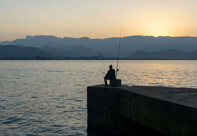 Silhouette man fishing on sea against sky during sunset