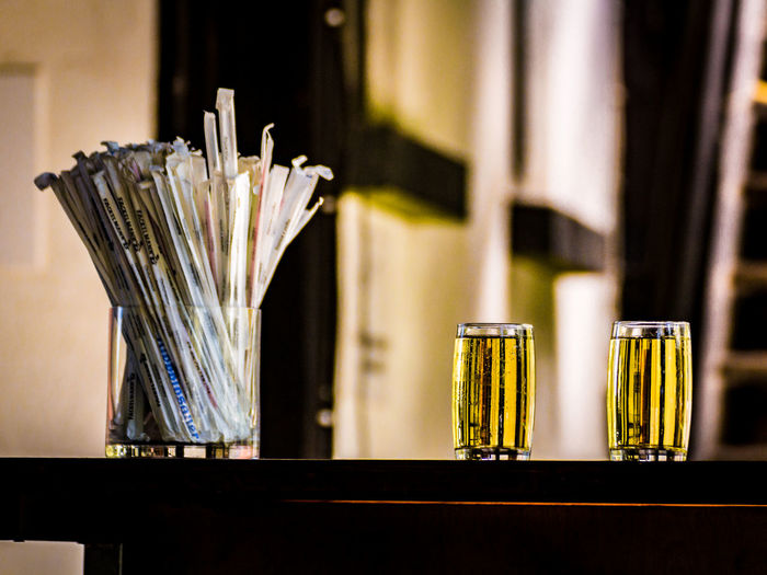 Packed drinking straws in container by drinks served on table