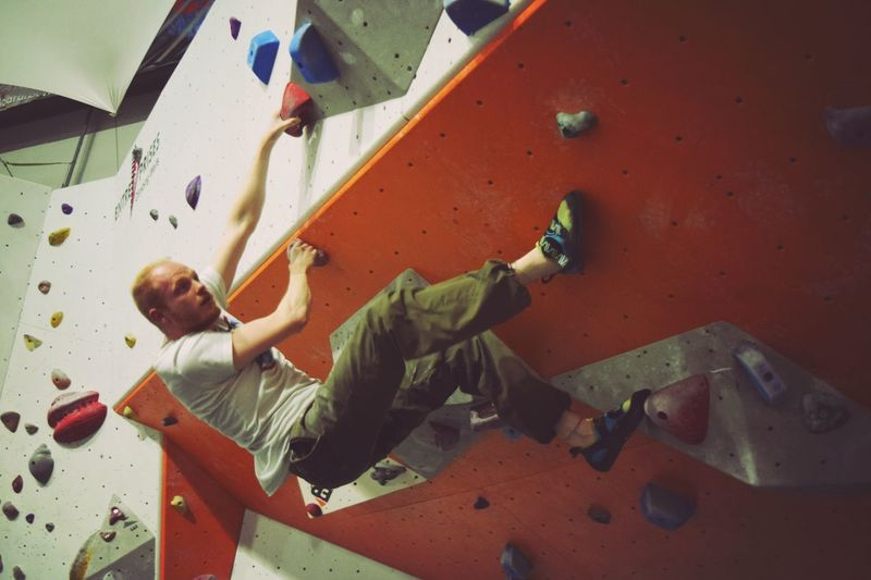 Low Angle View Of Athlete Climbing Rock Wall In Gym