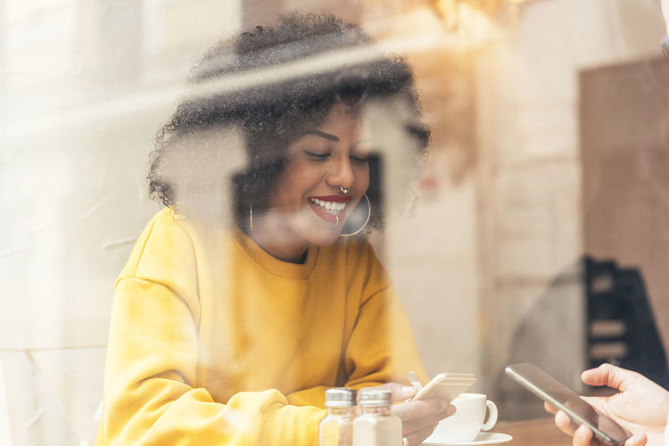 Smiling young woman using phone in cafe seen through window