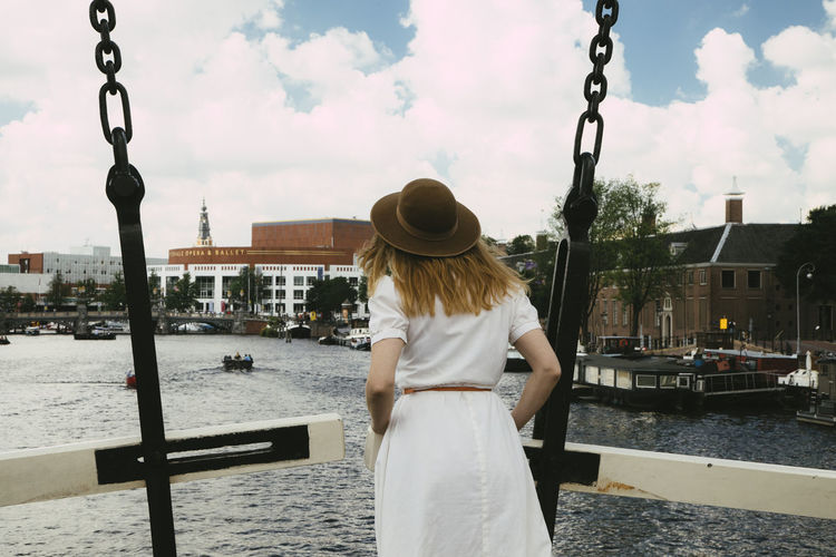 Rear view of woman standing by canal in city against sky