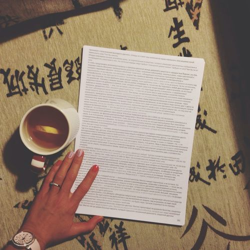 Close-up of woman reading document with lemon tea