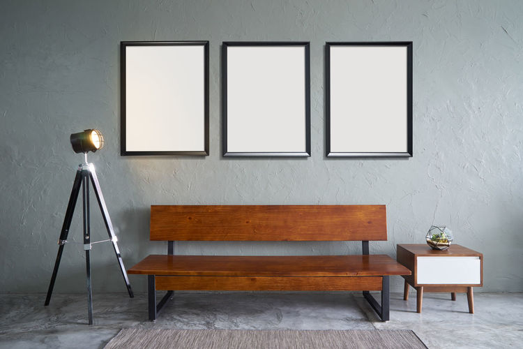 Bench Against Empty Picture Frames Hanging On Wall