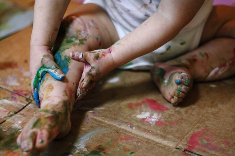Low section of playful child with hands and legs painted sitting on floor