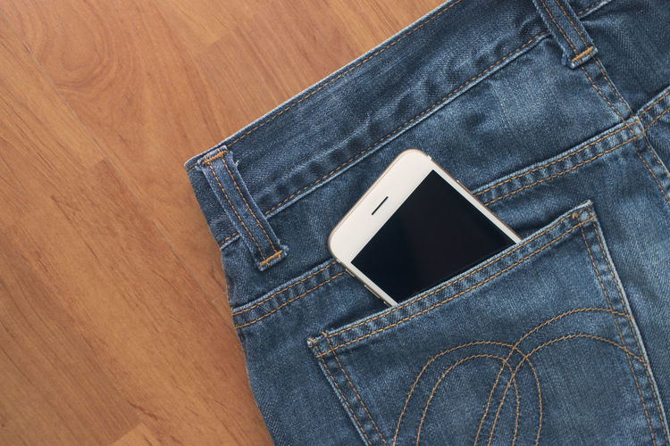 High Angle View Of Mobile Phone In Back Pocket Of Jeans Over Table