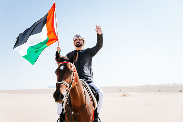 Man holding flag while riding horse at dessert