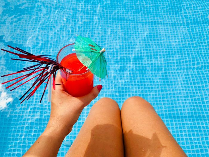 Midsection of woman holding drink while sitting by swimming pool