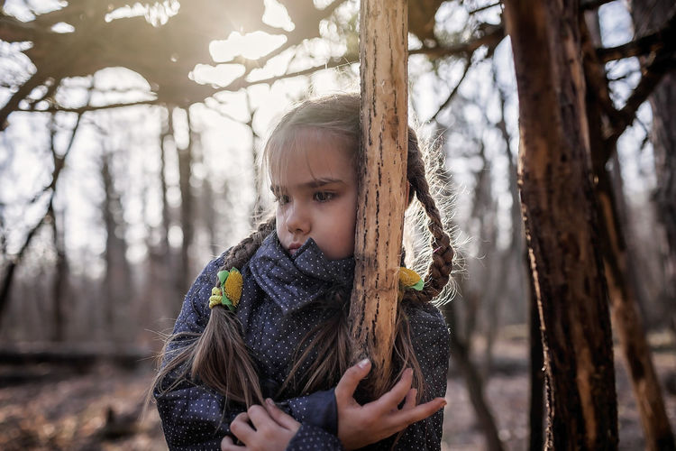 Portrait of girl holding tree trunk