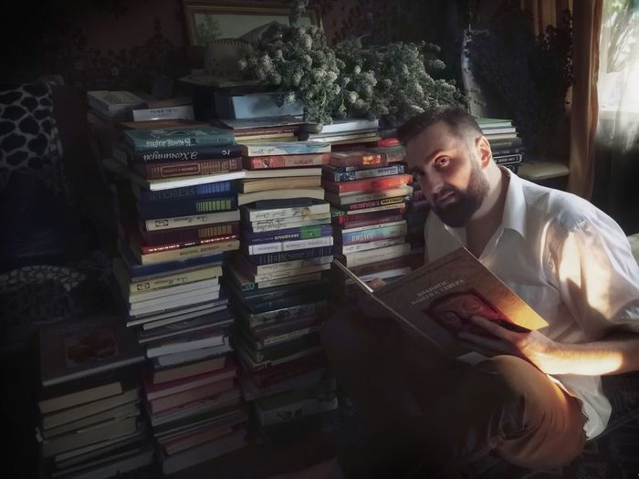 Young man sitting on book