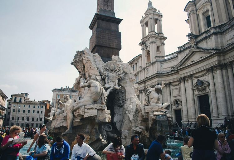 Tourist By Statue Fountain In Piazza Navona Against Sky