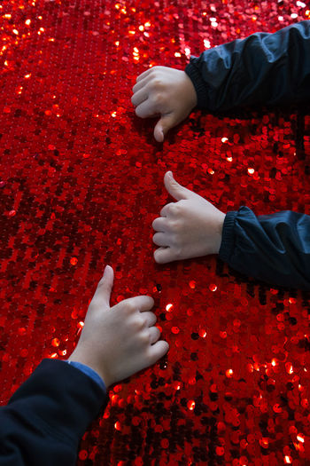 Cropped hands of children on red glitters