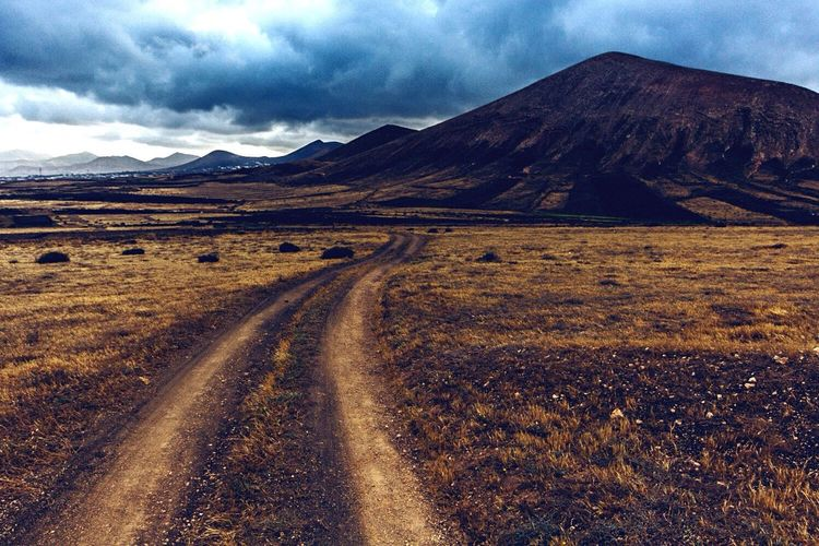 Dirt Road Along Landscape And Against Clouds