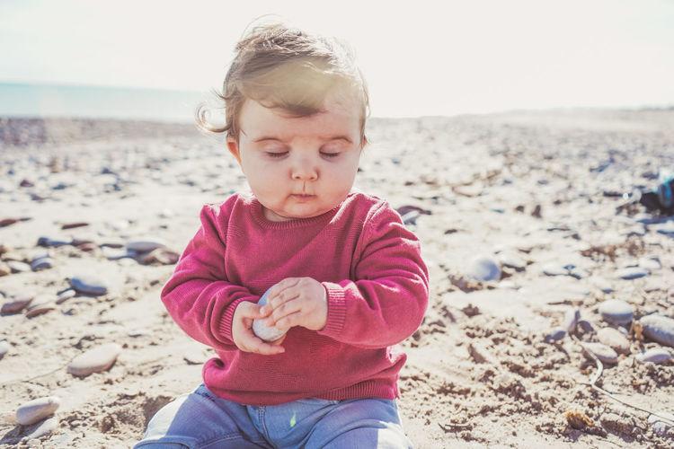Portrait of cute boy holding sand at beach