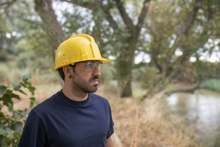 Man wearing hard hat standing against trees