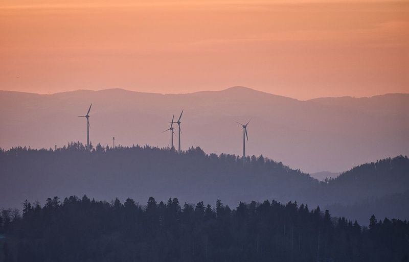Scenic view of silhouette mountains with wind power plant against sky during sunset
