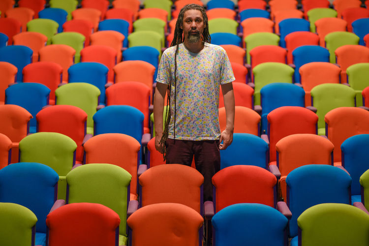 Man with dreadlocks standing between chairs