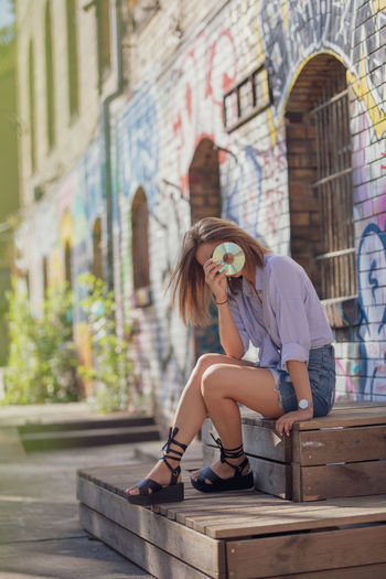 Young woman covering face with compact disc while sitting by graffiti