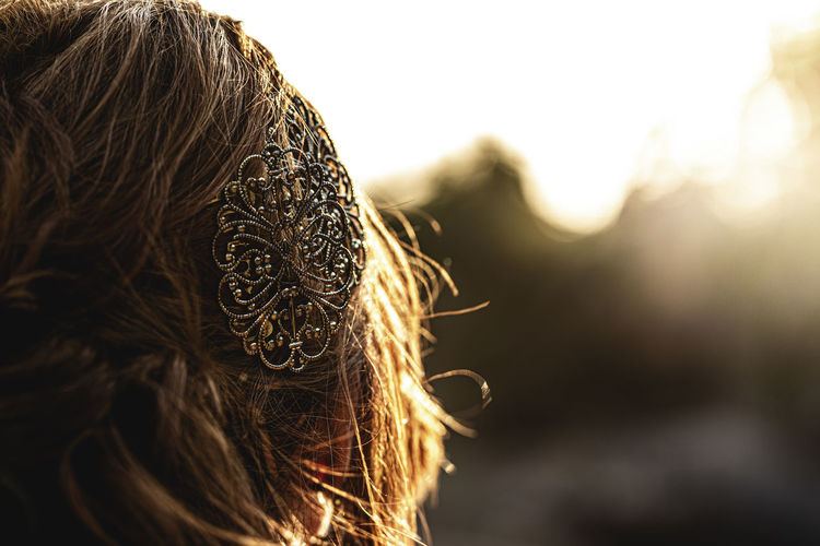 Close-up of woman wearing hair clip during sunset