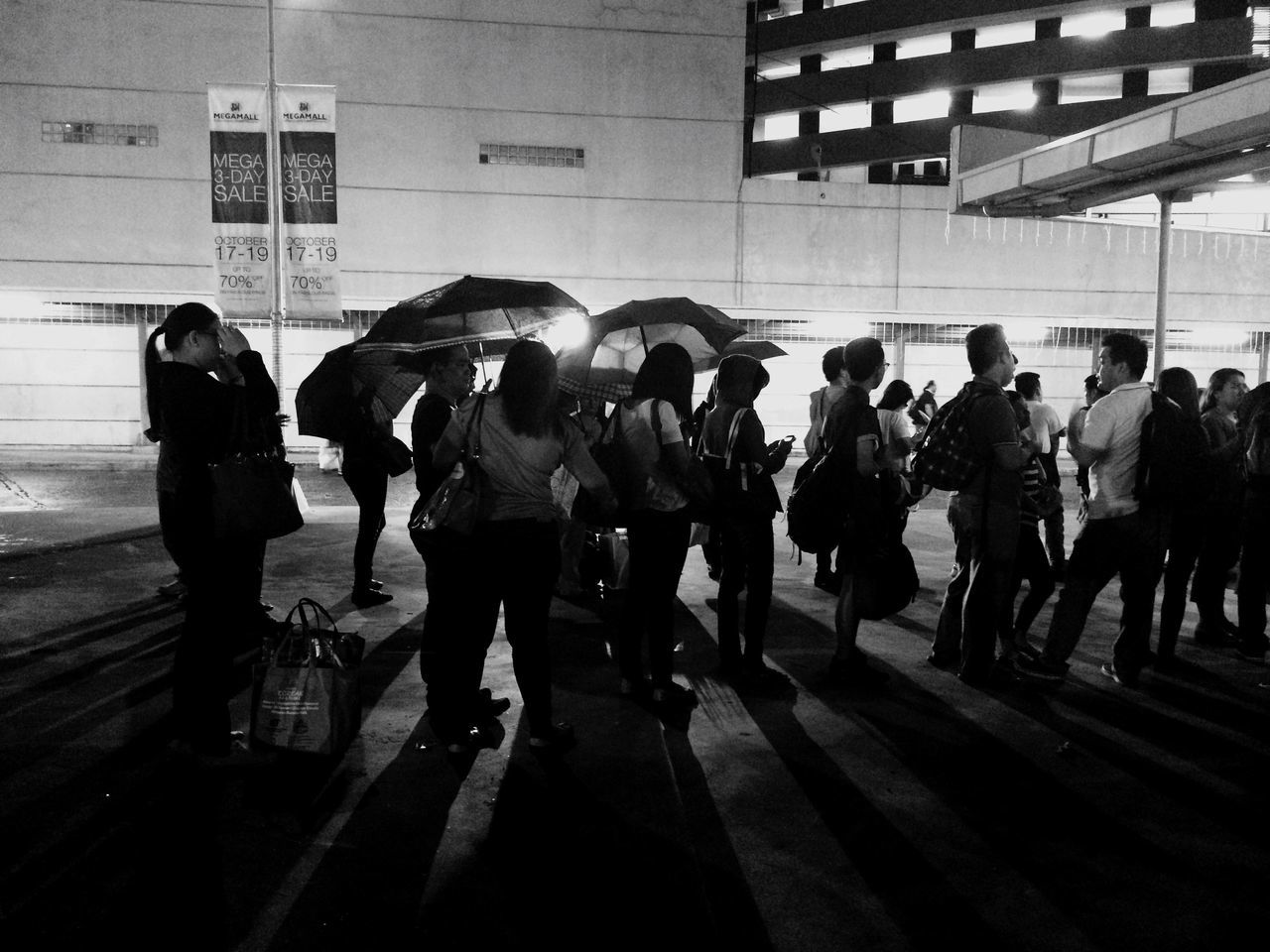 PEOPLE STANDING ON TILED FLOOR IN CORRIDOR