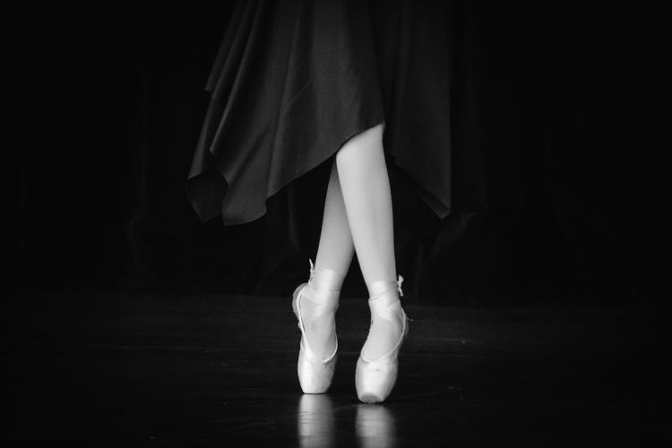 Low section of woman tiptoeing against black background