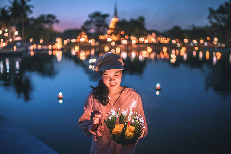 Happy loy krathong festival 2018. 🌕🌟 Loy krathong festival young smiling woman holding Krathong in your hand and bokeh background. Architecture Night Real People Nightphotography Happy Dusk Women Moon Happiness Celebration Standing Smiling Illuminated Emotion Loy Krathong Adult Front View Lifestyles Loy Krathong Festival One Person Casual Clothing Waist Up Leisure Activity Focus On Foreground Mid Adult