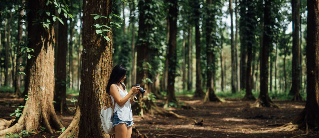 Tree Forest Land Plant Tree Trunk Trunk One Person WoodLand Lifestyles Standing Photography Themes Photography Photographer Looking At Camera Into The Woods Woods Wonderful Wandering Wanderlust Adventurous Calmness Checking Out Young And Free Fearless Traveller