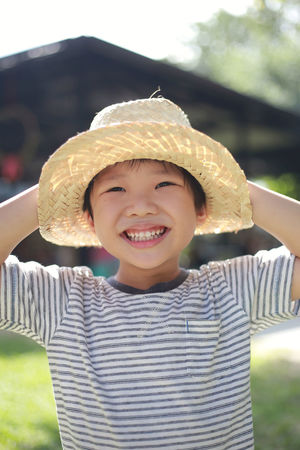 Cute asian boy wearing a hat and playing outside in the summer sun