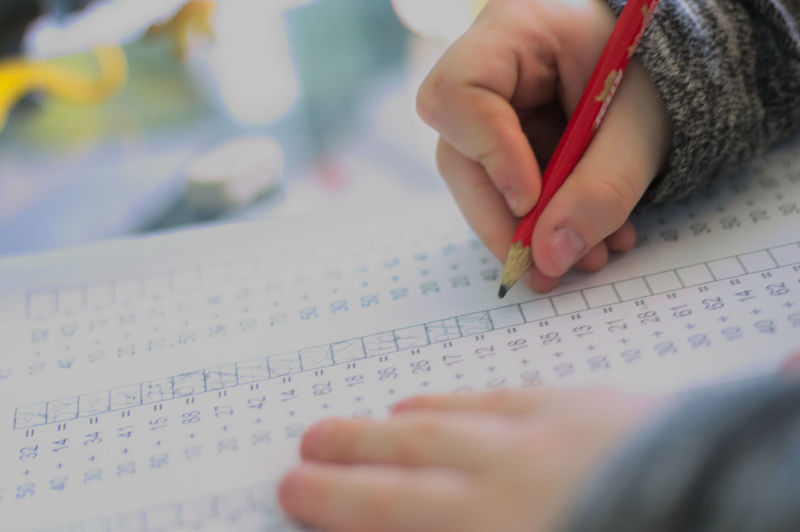 Cropped image of child writing on paper