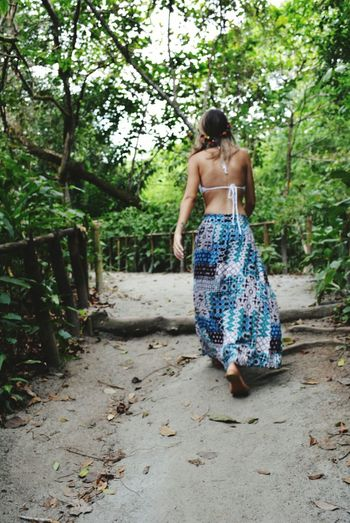 Rear view of woman walking on footpath amidst plant