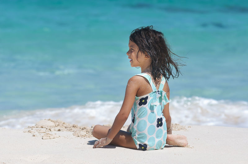 Girl looking away while sitting on beach