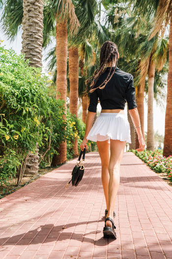 Rear view of young woman with braided hair  wearing stylish outfit walking in park