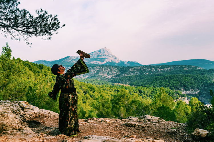 Woman with arms raised on mountain against sky