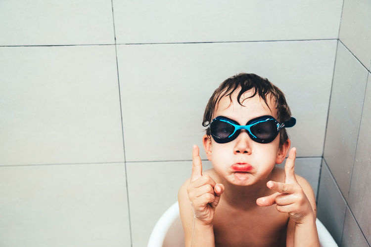 Boy wearing swimming goggles while sitting in bucket