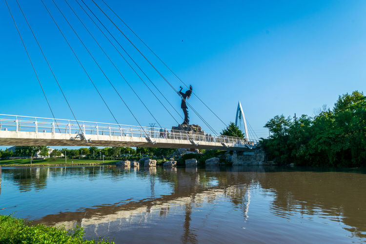 View of bridge over river against blue sky