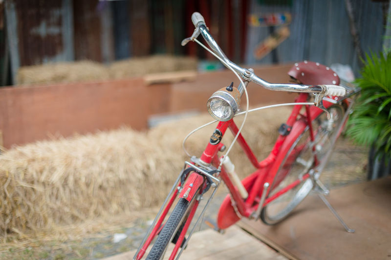 Close-up of bicycle leaning on field