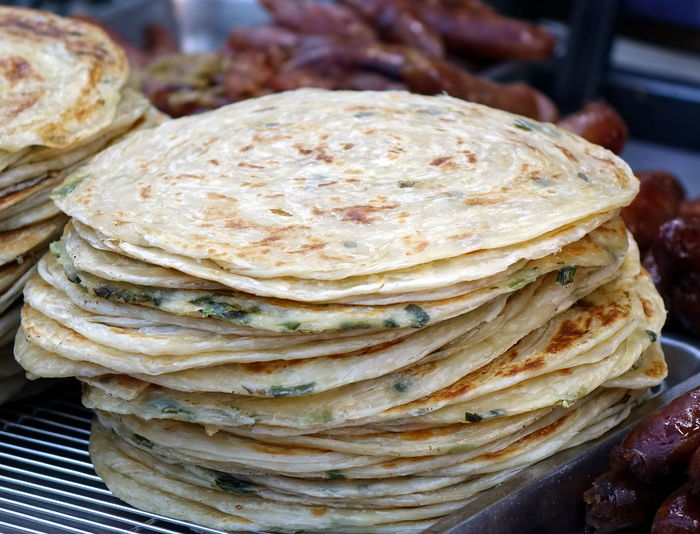 Chinese fried pancakes with leeks for sale at the market in Taiwan Chinese Food Fried Pancake Chives Food Leeks Market Stall Pancake Ready-to-eat Snack Food Stack Street Food Wrappers