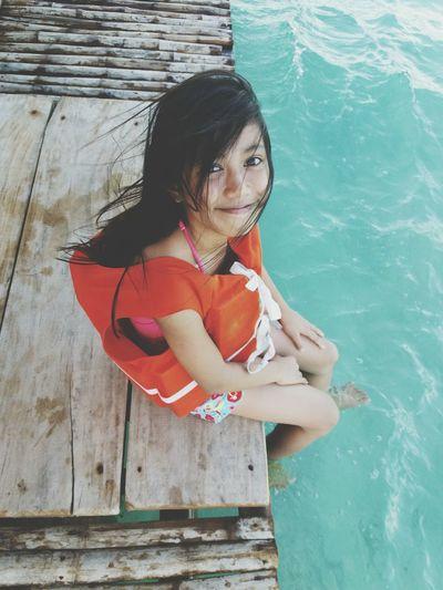 Portrait of smiling girl sitting on pier over lake