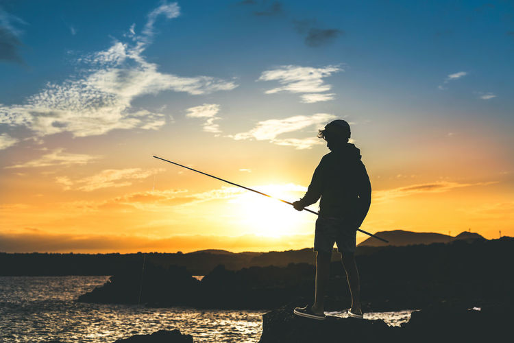 Boy fishing in sea against sky during sunset