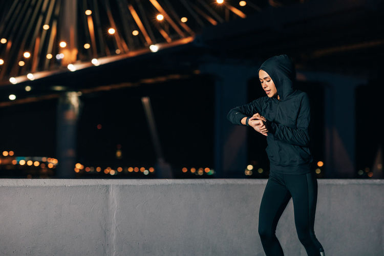 Woman looking at illuminated camera at night