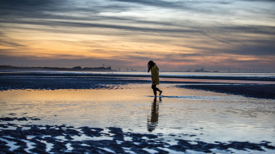 Side view of woman walking on shore against sky during sunset